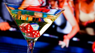 a cocktail with two red dice inside and casino goers in the background
