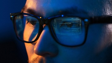 close up of the eyes of a man wearing glasses looking at a computer screen