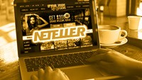 an open laptop with Grande Vegas Casino on the screen and the Neteller logo