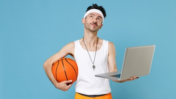 skinny guy wearing basketball clothes, holding a basketball and a laptop
